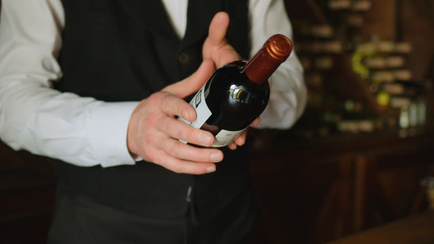 Attractive sommelier puting botlle of wine from hand to hand on the wood background with wine. Slow motion. Close up.