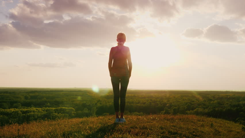 Silhouette of a woman standing on a hill top facing the sun. Against a background of a very beautiful valley. Back view. Concept - man and nature, active and healthy way of life, faith and religion #26785420