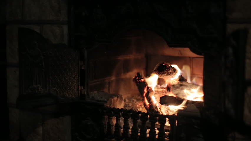 Burning fireplace making coziness at house in the evening. Stone walls and forged lattice make atmosphere of medieval castle