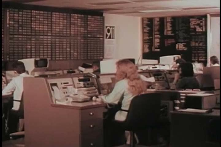 1970s: A woman working in a 911 emergency center fields a call for an ambulance in 1975. | Shutterstock HD Video #26832991