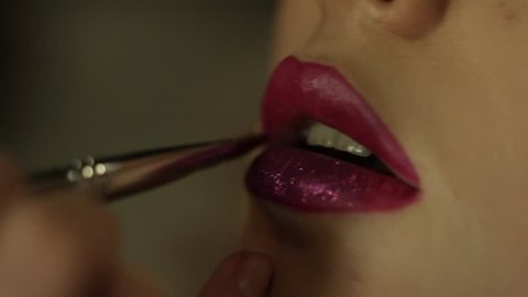 Female make-up artist apply purple glitter on pink lipstick with brush on a client's lips, close up.