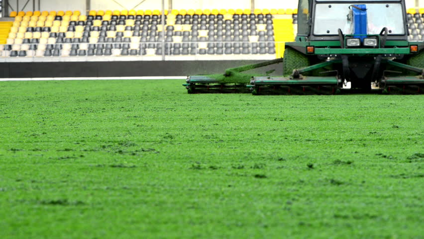 Mowing grass in a football stadium with an riding mower