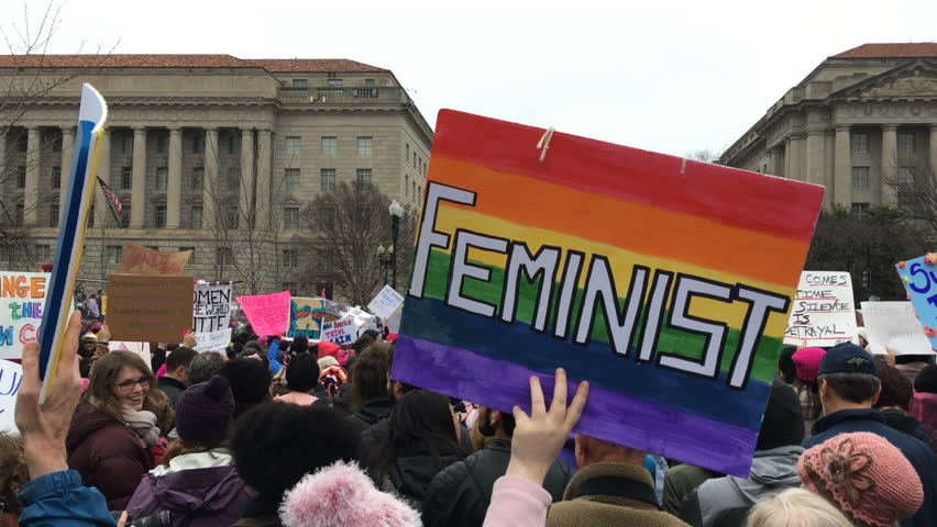 """A protester holds a """"Feminist"""" sign with the LGBTQ flag during the Women's March in Washington, DC Jan. 21, 2017."""