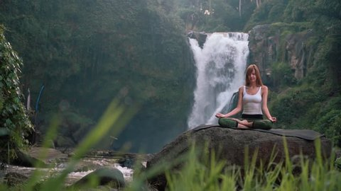 Woman doing yoga (Kapalbhati) in front of Tegenungan Waterfall, Ubud