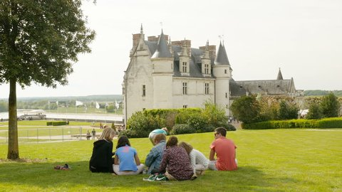 AMBOISE, FRANCE - CIRCA 2017: Unique footage of Royal Chateau de Amboise - Loire Valley - Castle of Amboise family having a picnic green grass Amboise castle in the background - advertising cinematic