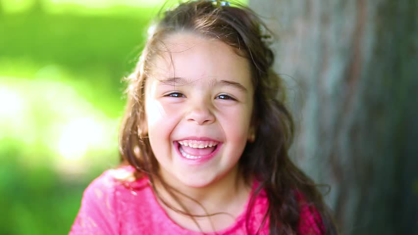 Closeup portrait of beautiful cute brunette caucasian little girl smiling and laughing while looking at camera. Real time full hd video footage.