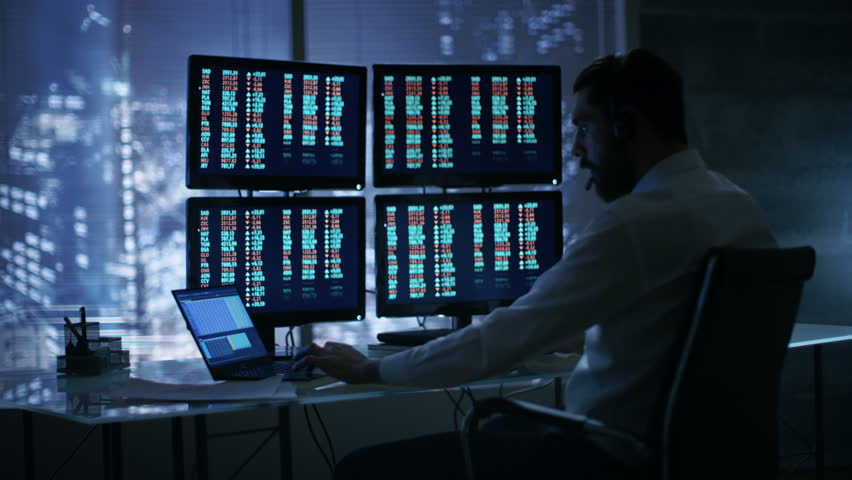 Late at Night Trader Reads Numbers on His Multiple Displays with Stock Information on Them, He Also Consults Clients with Headset On. In Background Big City Window View.