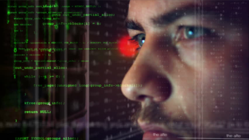 Male hacker working on a computer for cyber attack while green binary hacking code characters reflect on his face in a dark office room