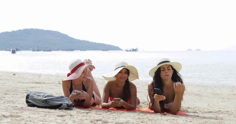 Three Girls Using Cell Smart Phone Lying On Beach Talking, Chatting Online Young Woman Communication Tourists On Summer Holiday Slow Motion 60 | Shutterstock HD Video #26946451