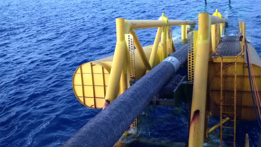 Underwater pipe laying moving on the stinger structure of pipelay accommodation barge at South China Sea, Sarawak, Malaysia in time lapse mode.