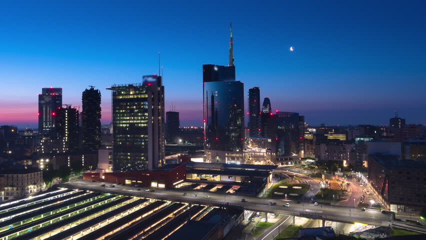 milan timelapse from night to day traffic running under skyscrapers