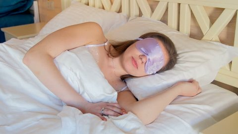 4k video of beautiful young woman taking off blindfold sleeping mask and sitting on bed