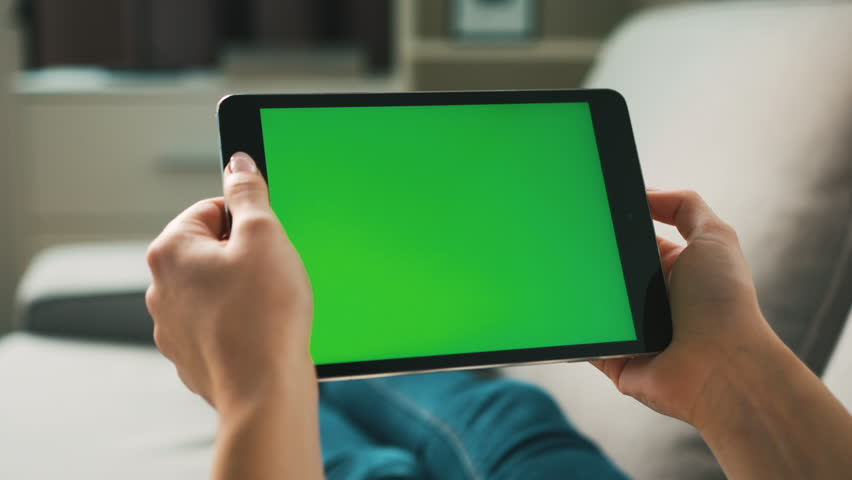 Woman hands using black tablet with green screen, lieng on sofa at home. View from the back. Chroma key. Close up.