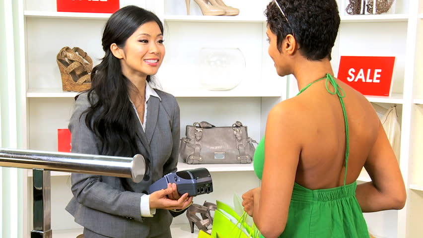 African American female paying Asian Chinese boutique owner with credit card
