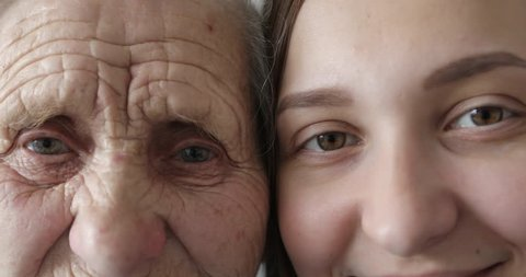 Old and young face. Grandmother and granddaughter looking together at camera. Close-up. 4K.