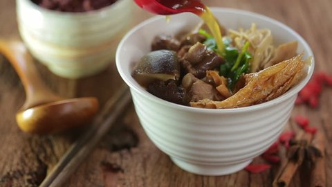 Bak-kut-teh is a pork rib dish cooked in broth popularly served in Malaysia and Singapore and Southern Thailand. Chinese hot soup with herbs on rustic wood.