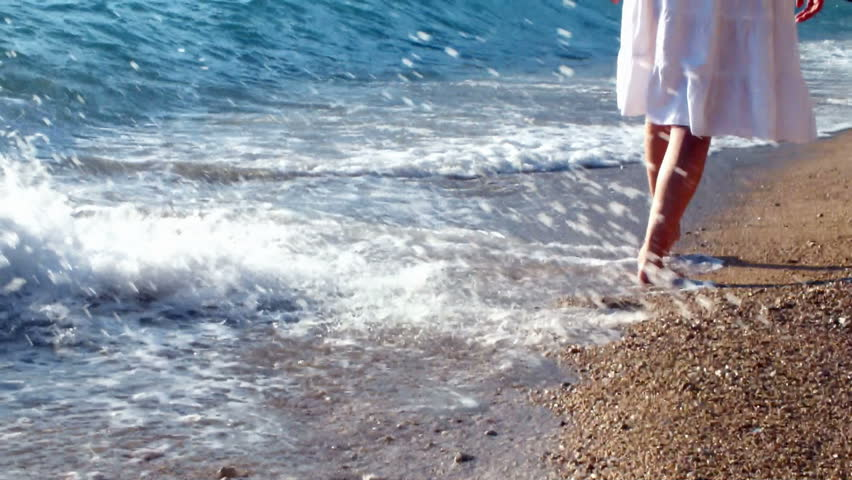 woman walks along the coast, washed by the waves of the sea, leaving footprints in the sand #2701541