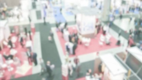 Panoramic view of a trade show with people visiting the exhibition stands. Background with an intentional blur effect applied. Humans and location not recognizable. Time lapse.