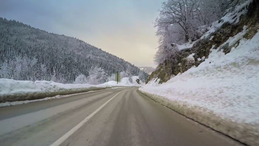 POV vehicle drive across beautiful countryside landscape with mountains range, winter snow, wet curvy road, forest trees and cloudy sky, car travel point of view   Shutterstock HD Video #27056761