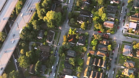 Overhead right pan across houses, yards and cars along suburban street