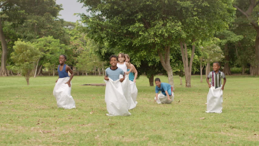 Elementary school teacher and kids having fun and playing sack race in city park. Summer camp fun
