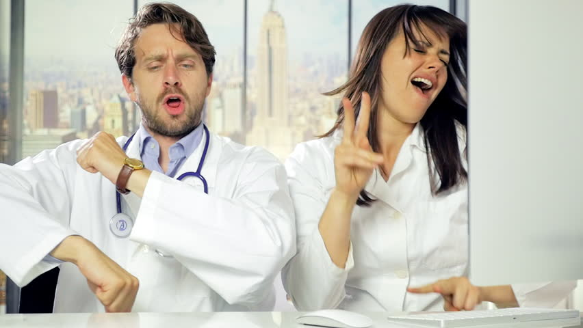 Man and woman doctor dancing and laughing like crazy in office in city