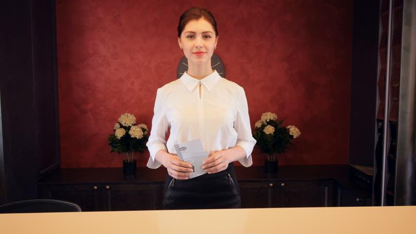 Receptionist at hotel reception desk meet guests. 4K.