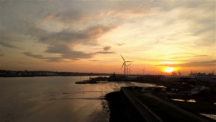 Sunset over The Port of Tilbury, Essex, UK; aerial drone reveal. Rising aerial video footage of Tilbury Docks, east of London on the River Thames, with wind turbines spinning slowly in the wind.