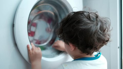 baby two years old boy looking washing machine at home in spin washing program. Home appliances.