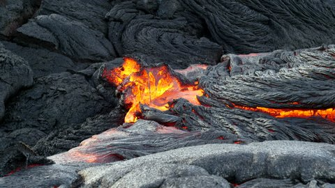 Surface flow lava oozes out of the nooks and crannies dried lava during an eruption from Kilauea volcano.