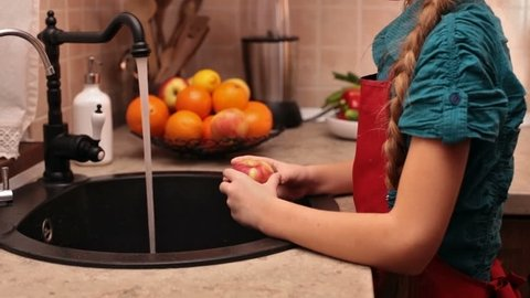 Little girl washing an apple at the kitchen sink - taking a bite of the fruit, camera tilts up from hands to face