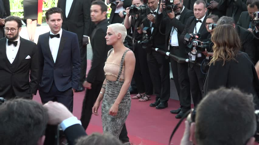 Kristen Stewart smiling, with gold top and long green Chanel dress, at the premiere of 120 Beats Per Minute at the Cannes Film Festival, 5/20/2017