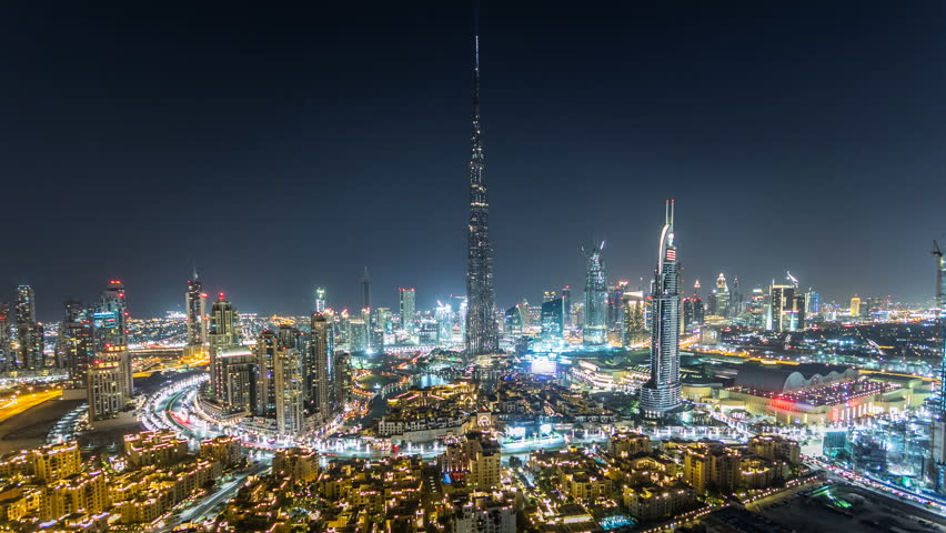 Dubai Downtown night timelapse with Burj Khalifa and other towers paniramic view from the top in Dubai, United Arab Emirates. Traffic on circle road and music fountain show