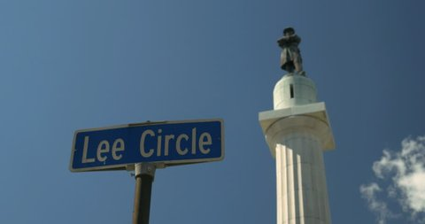 Lee circle Street sign with General Robert E Lee Confederate statue in background with blue sky. The statue was removed by the city on May 19th 2017 4K