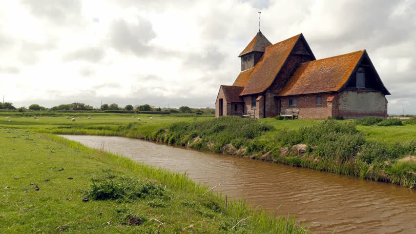 Old creepy church by water, medieval remote church, with fast moving clouds obscuring the daylight.