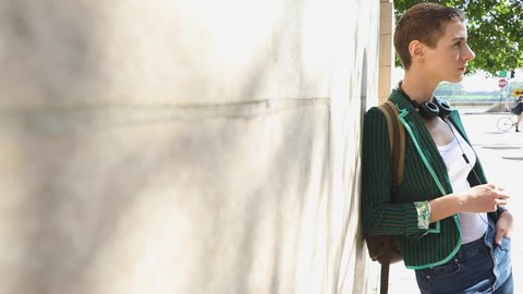 Woman in the city leaning on a wall. Portrait of a beautiful young woman with short hair, wearing a green jacket and bringing a backpack looking at camera, slow motion. Travel and lifestyle concepts.