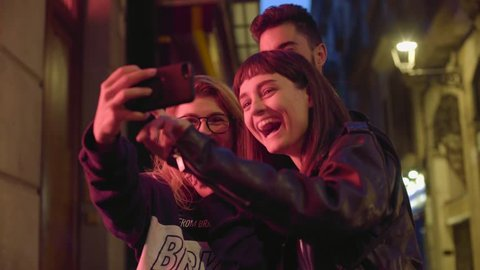 Three happy traveller friends on night street with red light smile and laugh while trying to take selfie to their social accounts or video stories with face masks.