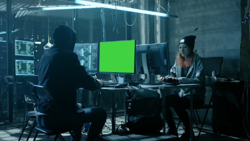 Team of Internationally Wanted Teenage Hackers with Green Screen Mock-up Display Infect Servers and Infrastructure with Virus. Their Hideout is Dark, Neon Lit and Has Multiple Displays. RED Cinema UHD | Shutterstock HD Video #27244621
