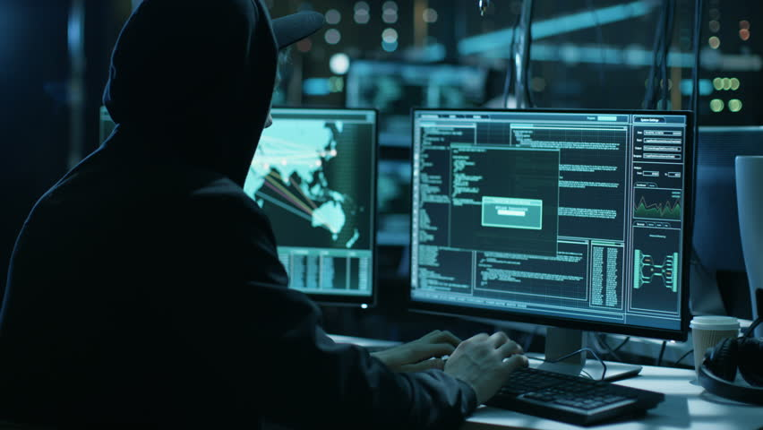 Team of Internationally Wanted Teenage Hackers Infect Servers and Infrastructure with Malware. Their Hideout is Dark, Neon Lit and Has Multiple Displays. Shot on RED EPIC-W 8K Helium Cinema Camera.   Shutterstock HD Video #27247381