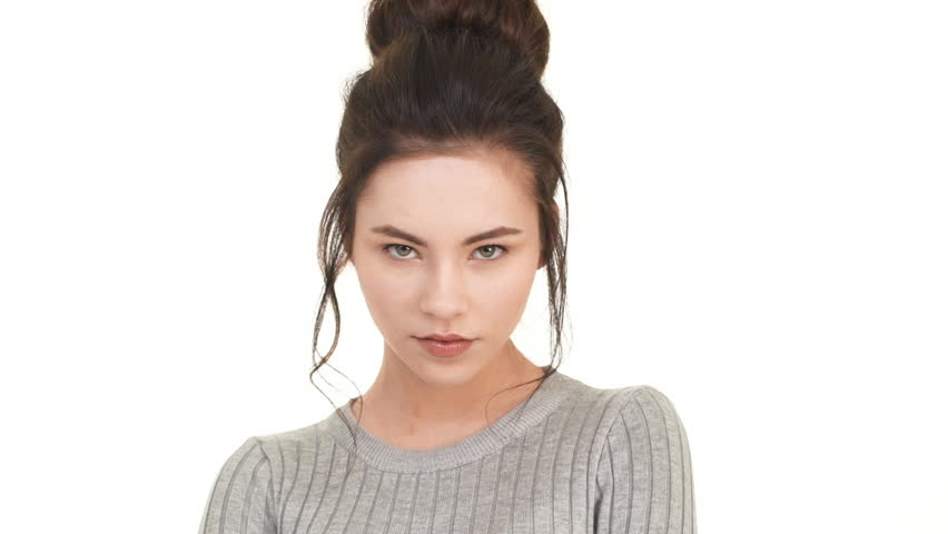 Beautiful Caucasian brunette girl looking straight at camera and pointing  to look right into eyes. Footage on white background in slowmotion