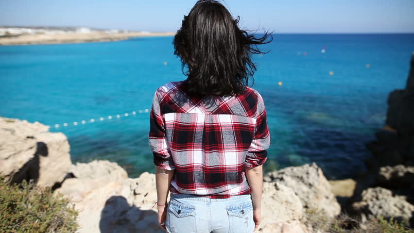 Back view of young woman with wind in her hair standing on cliff and enjoying beautiful sea view. Relax concept | Shutterstock HD Video #27259711