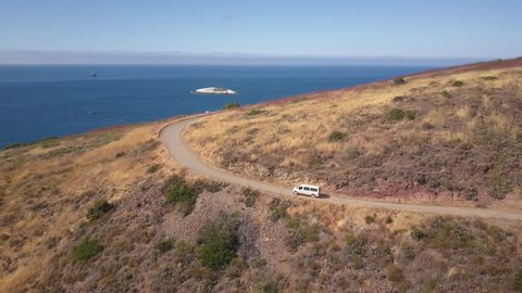 Aerial shot following a white van on a dirt road along the coast of the Pacific ocean. Rocky terrain, with a couple rocky islands visible in ocean.