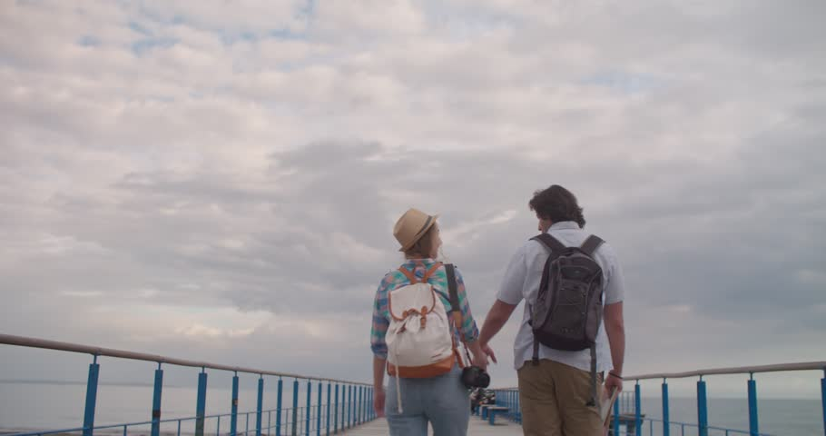 Young romantic explorers couple holding hands and walking on wooden pier by the sea