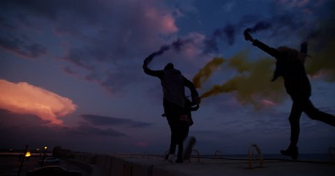 Group of teen friends partying with smoke grenades in the city after sunset