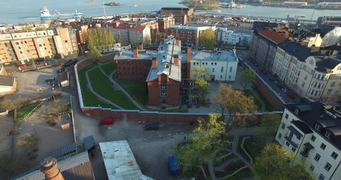 Aerial view drone footage of Helsinki old prison, bay area with boats and cruise liners near sea terminal and harbour with city skyline and Baltic Sea view in the capital of Finland, northern Europe
