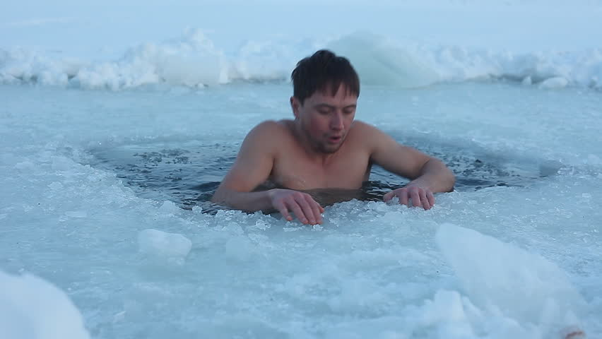 Young man having recreation swim in an ice hole