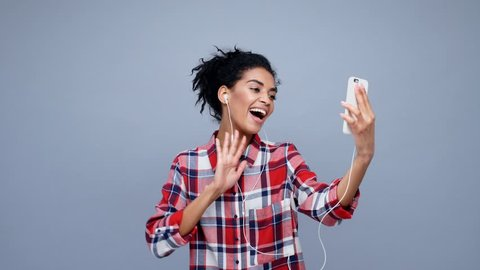 Happy young woman making videocall with phone and headphones and waving hand isolated