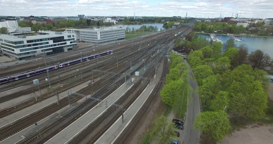 Aerial of Helsinki central railway station area, gardens and rail tracks with trains arriving and urban city skyline view in the capital of Finland, northern Europe