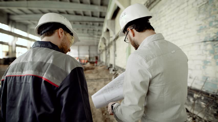 The customer in a protective helmet verifies the work of builders on the object under construction, people walk through the building of the former factory