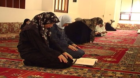 LEBANON - CIRCA 2006: View of a Shia Lebanese woman prostrating herself in prayer and kissing a circular stone or turbah used during salat (daily Islamic prayer), in the women's section of a mosque.